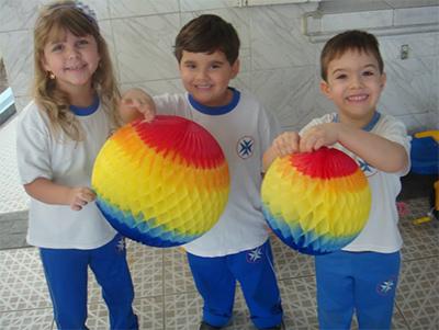 Três crianças com bolas coloridas.