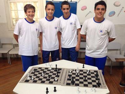 Quatro garotos com mesa e dois tabuleiros de xadrez.